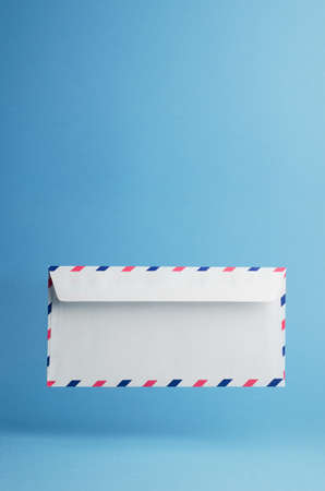background blue: Envelope falling on the ground, blue background with negative space Stock Photo