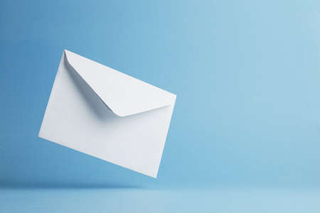 Envelope falling on the ground, blue background with negative space Imagens