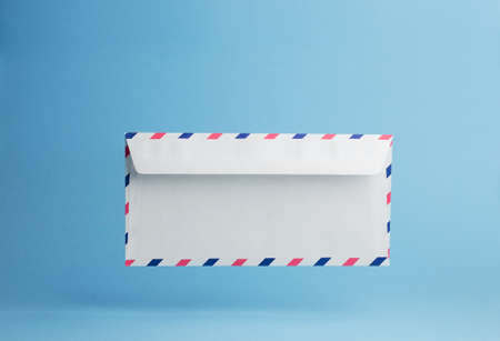 negative space: Envelope falling on the ground, blue background with negative space Stock Photo