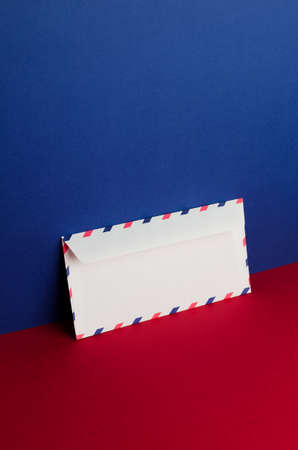 blue background: Envelope tilted over blue and red background with negative space