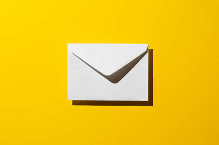 harsh: Envelope with harsh shadow over yellow background, top view