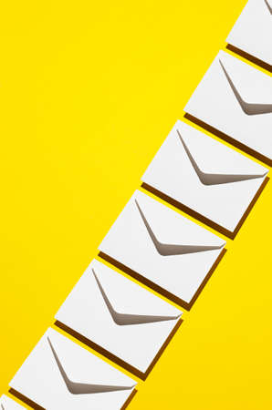 negative space: Envelopes pattern over yellow background, above view with negative space Stock Photo