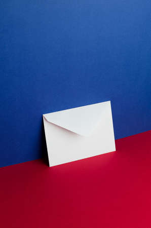 red and blue: Envelope tilted over blue and red background with negative space