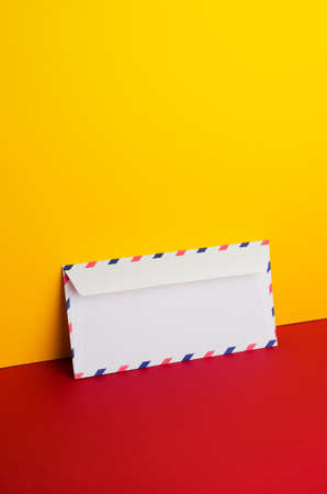 tilted: Envelope tilted over yellow and red background with negative space Stock Photo