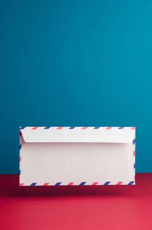 par avion: Envelope in the air over blue and red background with negative space