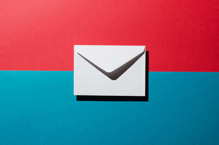 harsh: Envelope with harsh shadow over red and blue background, top view