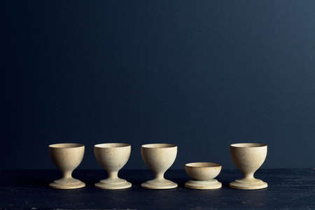 egg cups: Empty Egg cups organized in a row over dark background with negative space Stock Photo