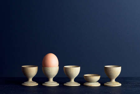 negative space: Egg cups and a single brown egg organized in a row over dark background with negative space