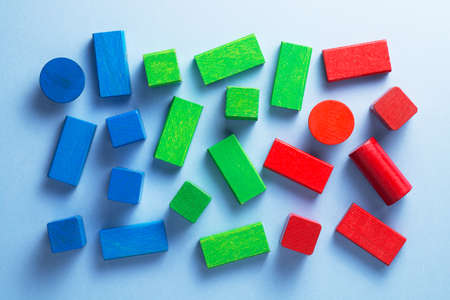 disorganized: Colorful wooden cubes disorganized over blue background, top view