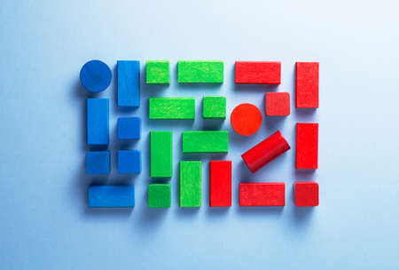 cylinder block: Colorful wooden cubes organized over blue background, top view