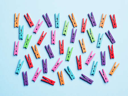 disorganized: Laundry clips disorganized over blue background, top view
