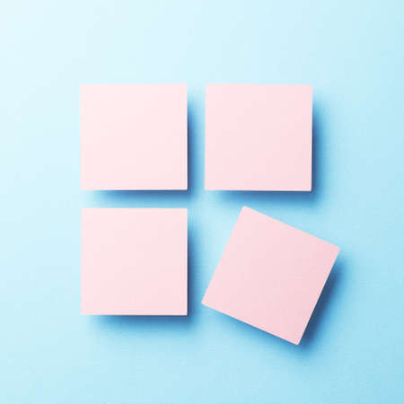 tilted view: Paper squares organized over blue background, top view Stock Photo