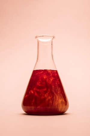 Erlenmeyer flask over light orange background Stockfoto