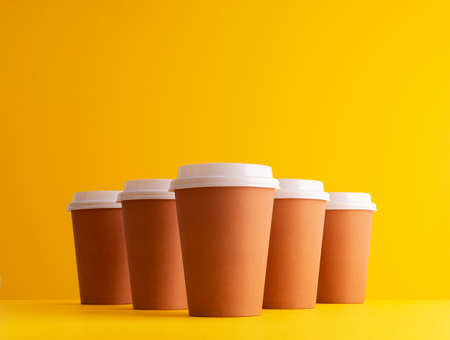 Multiple disposable coffee cups organized in a row over yellow background Foto de archivo - 118563837