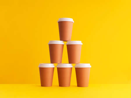 Multiple disposable coffee cups organized in a stack over yellow background Foto de archivo - 118563839