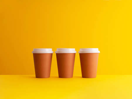 Multiple disposable coffee cups organized in a row over yellow background Foto de archivo - 118563924