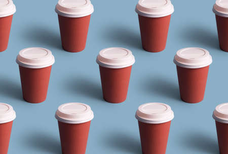 Disposable coffee cups organized in a row over blue background Foto de archivo - 118563926