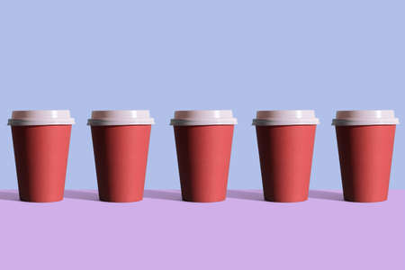 Disposable coffee cups organized in a row over blue background Foto de archivo - 118563927