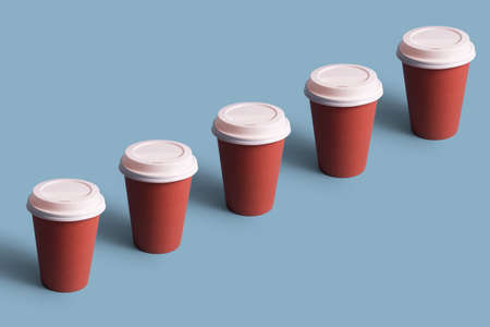Disposable coffee cups organized in a row over blue background Foto de archivo - 118563929