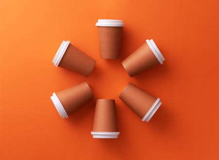 Multiple disposable coffee cups organized in a circle orange background Foto de archivo - 118563931