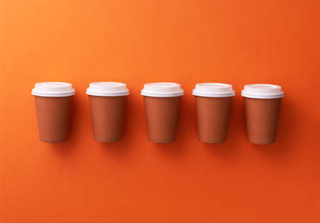 Multiple disposable coffee cups organized over orange background Foto de archivo - 118563933
