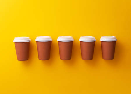 Multiple disposable coffee cups organized over yellow background Foto de archivo - 118563936
