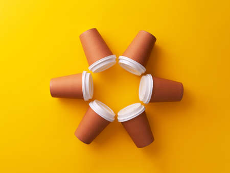 Multiple disposable coffee cups organized in a circle over yellow background Foto de archivo - 118563937