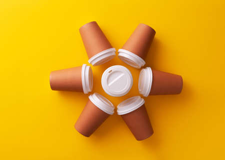 Multiple disposable coffee cups organized in a circle over yellow background Фото со стока