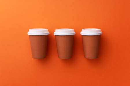 Multiple disposable coffee cups organized over orange background Foto de archivo - 118563940