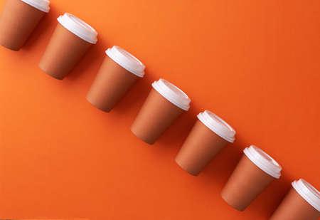 Multiple disposable coffee cups organized over orange background Foto de archivo - 118563941