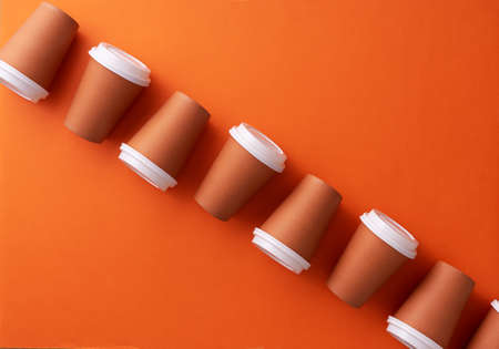 Multiple disposable coffee cups organized over orange background Foto de archivo - 118563942