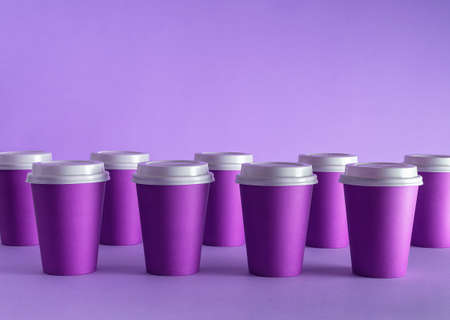 Disposable coffee cups organized over purple background Foto de archivo - 118563973
