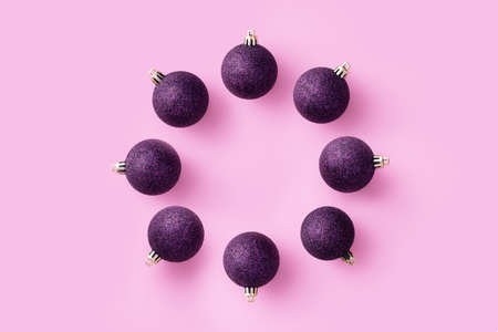 Purple Christmas baubles organized in a circle over pink background, top view