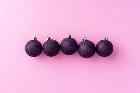Purple Christmas baubles organized in a row over pink background, top view Foto de archivo - 126456338