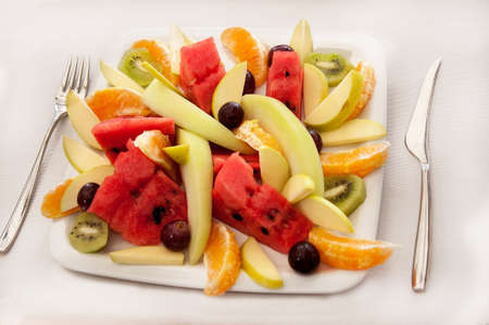 Fruit salad with fork and knife isolated on white background Stock Photo - 7504597