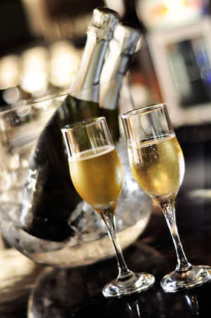 Isolated glasses of champagne with bottle background photo