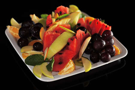 prunella: Isolated plate with lots of fruits on black background