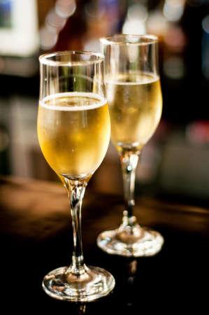 bebidas alcoh�licas: 2 vasos de champ�n en bar fondo