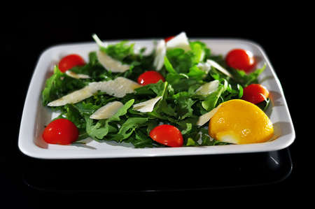 Salad with cheese and cherry tomatoes isolated on black photo