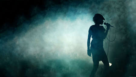 stage performer: Singing woman silhouette with smoke background Stock Photo