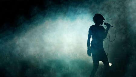 backlit: Vrouw silhouet met rook achtergrond zang  Stockfoto