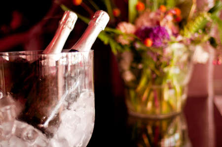 Two bottles of champagne in ice bucket with flowers in background. photo