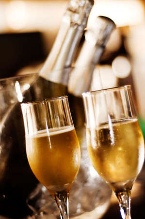 Close-up of two champagne glasses with bottle on background photo