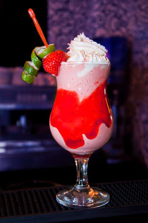long cocktail with whipped cream, strawberries, lime and syrup photo
