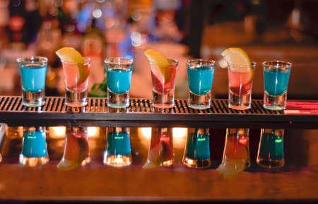 sparo: Riga di colpi sulla barra, tequila e blue curacao Archivio Fotografico