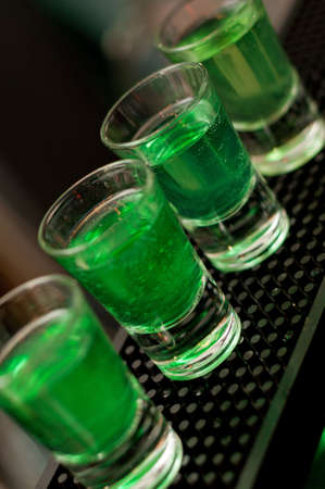 Green liquid in shot glasses standing on the counter.