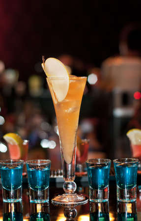 Long cocktail with four curacao shots photo