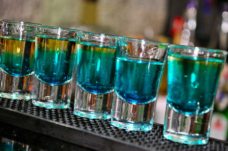 rich flavor: Blue drink in shot glasses standing on the counter