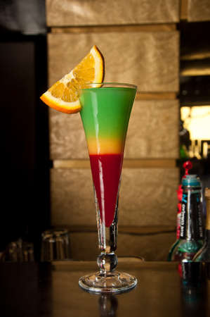 Cheerful Summer cocktail with slice of orange and bar background photo