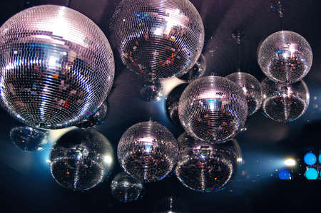Shiny disco balls in a nightclub with colorful reflections
